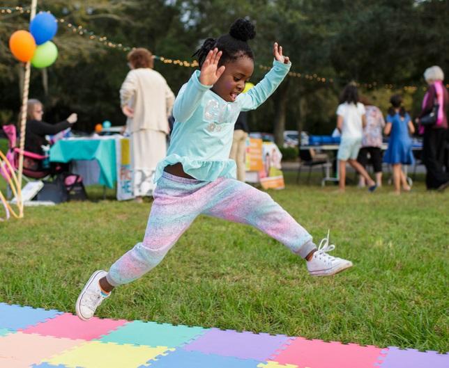 Littler girl jumping at a birthday celebration