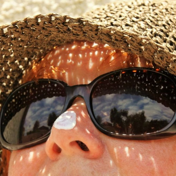 A child wearing sunglasses and sun hat with sunscreen at the tip of his nose.